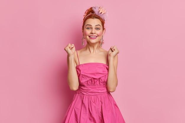 Mulher bonita e alegre com cabelo ruivo e maquiagem fecha os punhos alegra algo vestido com um vestido festivo e bandana tem poses de expressão feliz