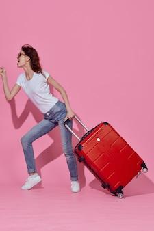 Mulher bonita e alegre com mala vermelha, passaporte e passagem de avião, viaja com fundo rosa