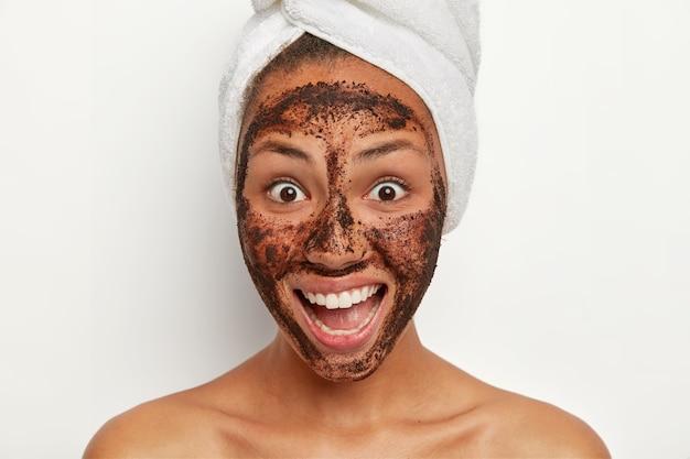 Mulher bonita e alegre com pele saudável e fresca, sorri amplamente, parece com uma reação de surpresa feliz, aplica máscara facial de esfoliante de café para reduzir manchas escuras na pele, faz terapia de spa após o banho