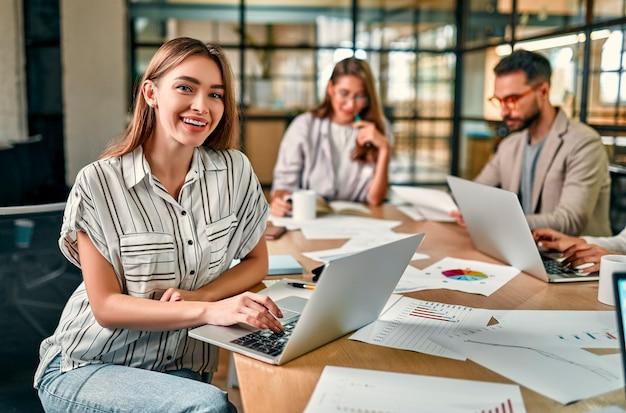 Mulher bonita e alegre com um laptop com um sorriso olha para a câmera, sentada em uma mesa de escritório com seus colegas.