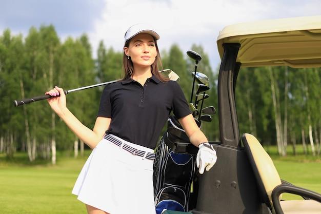 Mulher bonita e alegre em pé perto no carrinho de golfe.