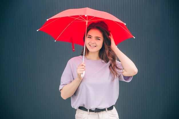Mulher bonita e alegre sob o guarda-chuva vermelho para proteção contra chuva