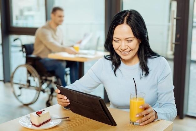 Mulher bonita e alerta de cabelos escuros sorrindo, bebendo suco e usando o tablet enquanto está sentada em um café e um homem na cadeira de rodas sentado ao fundo