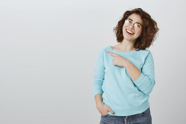 Mulher bonita e amigável de óculos mostrando o caminho, apontando o dedo para a esquerda