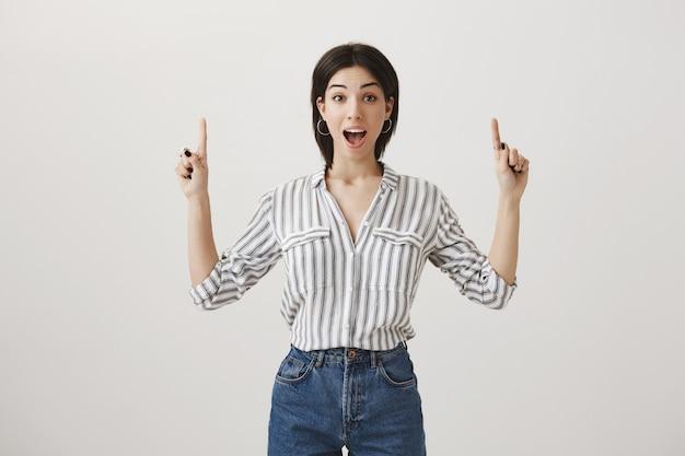 Mulher bonita e animada mostrando copyspace, apontando o dedo para cima