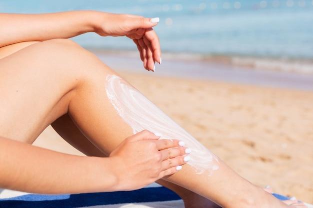 Mulher bonita é aplicar protetor solar na perna com a mão relaxante na espreguiçadeira à beira-mar