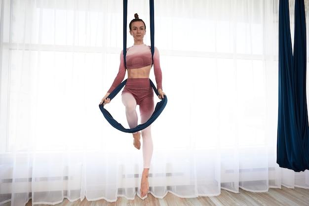 Mulher bonita e atlética, com um top e leggings, faz exercícios de ioga antigravitacional em uma espaçosa academia com janelas panorâmicas