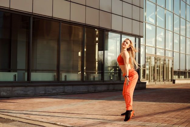 Mulher bonita e atlética está dançando, se aquecendo antes do treino em frente ao prédio urbano.