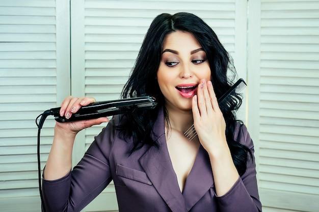 Mulher bonita e atraente, cabeleireira estilista fazendo um penteado e segurando o modelador de cabelo para o cabelo nas mãos no estúdio de salão de beleza