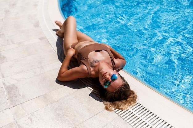 Mulher bonita e atraente com cabelos loiros de biquíni relaxando na piscina em um maiô marrom, mentiras e descansos