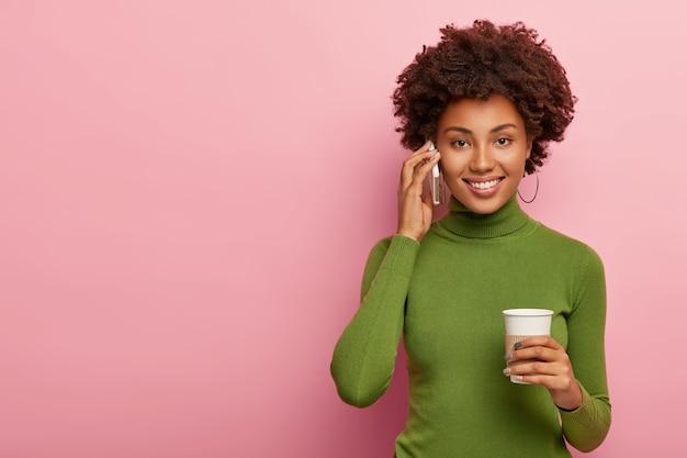 Mulher bonita e atraente com penteado afro, liga para um amigo pelo celular, bebe café para viagem, tem uma conversa agradável, sorri feliz, discute boas notícias, usa um macacão verde casual, posa dentro de casa