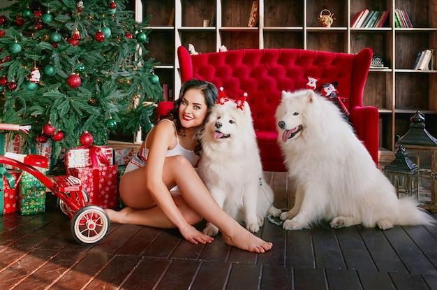 Mulher bonita e atraente em cueca branca com caixa de presente nos braços, sentada no sofá vermelho