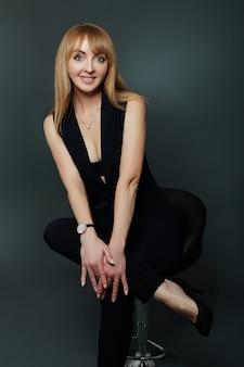 Mulher bonita e atraente em um terno preto sorrindo e posando em um fundo escuro