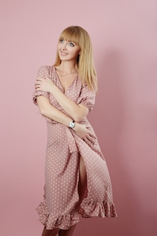 Mulher bonita e atraente em um vestido leve de verão, sorrindo e posando em um fundo rosa claro