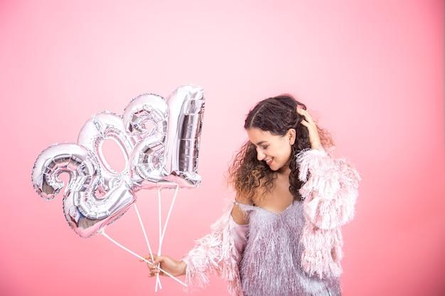 Mulher bonita e atraente morena com cabelo encaracolado vestida festivamente posando em uma parede rosa com balões prateados para o conceito de ano novo