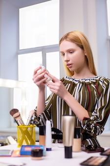 Mulher bonita e atraente olhando para o frasco com loção enquanto escolhe os cosméticos