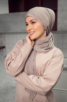 Mulher bonita e bem cuidada em um hijab desvia o olhar e sorri