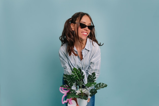 Mulher bonita e bonita com cabelo escuro, vestindo camisa azul, segurando um vaso de flores e sorrindo, posando contra uma parede azul
