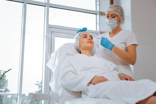 Mulher bonita e bonita deitada na cama médica enquanto toma uma injeção de beleza