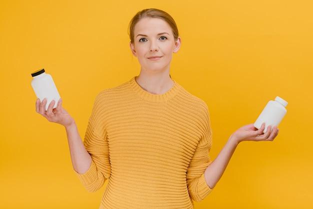 Mulher bonita e bonita escolhendo um frasco de pílulas médicas ou vitaminas vestida casualmente