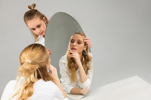Mulher bonita e bonita focada, apoiada na mão enquanto observa sua aparência no espelho
