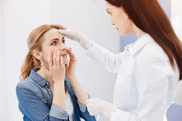 Mulher bonita e bonita segurando seu rosto e olhando para o médico enquanto quer fazer uma cirurgia plástica