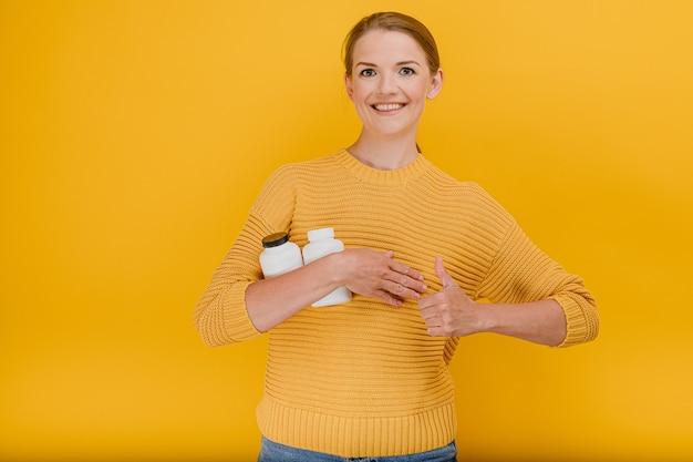 Mulher bonita e bonita segurando um frasco de pílulas médicas ou vitaminas vestida casualmente
