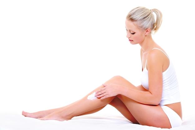 Mulher bonita e bonita sentada na cama aplicando creme hidratante nas pernas magras