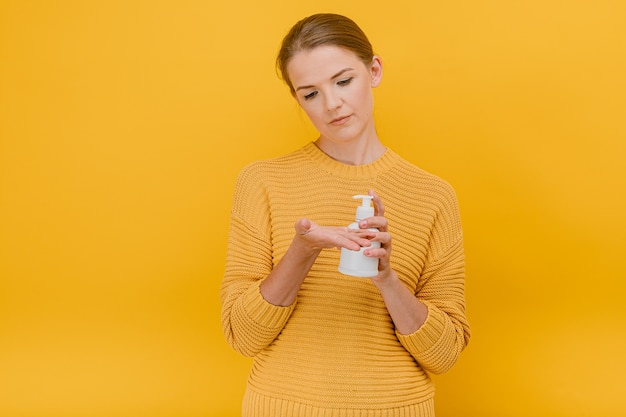 Mulher bonita e bonita vestida casualmente usa um desinfetante anti-séptico ou sabonete líquido em seu conceito de limpeza de mãos em pé Foto Premium