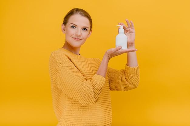 Mulher bonita e bonita vestida casualmente usa um desinfetante anti-séptico ou sabonete líquido