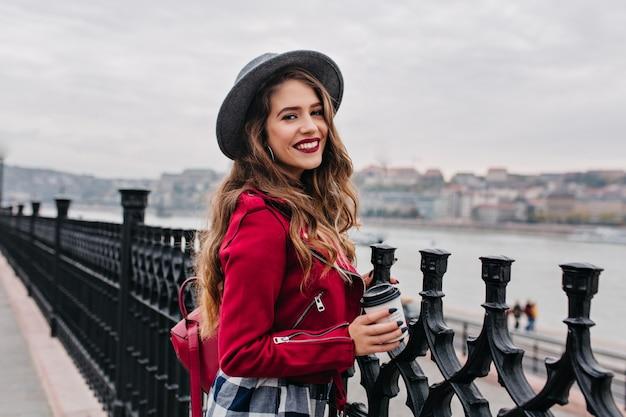 Mulher bonita e cacheada com maquiagem brilhante, apreciando a vista da cidade da ponte em dia de outono