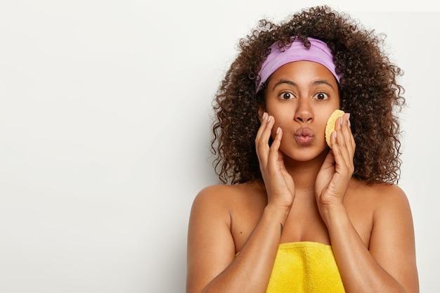 Mulher bonita e cacheada mantém os lábios dobrados, enrolada em uma toalha macia, quer ter uma pele lisa e fresca, usa esponja cosmética para limpar o rosto, usa bandana