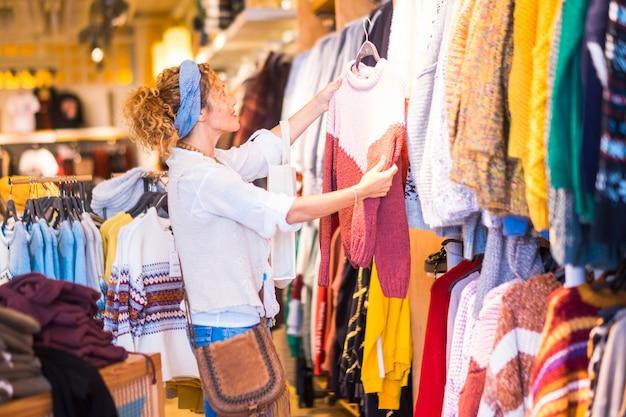 Mulher bonita e cacheada procurando um suéter em uma grande loja em um centro comercial