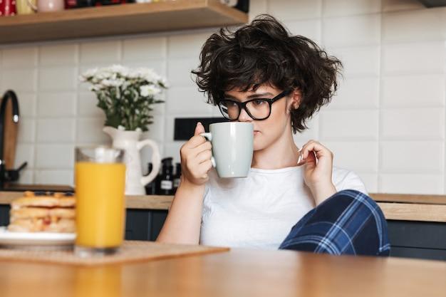 Mulher bonita e cacheada sentada na cozinha tomando chá