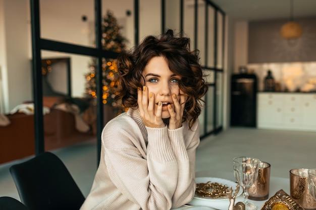 Mulher bonita e charmosa com penteado ondulado em camisa, posando com emoções de surpresa enquanto está sentado à mesa de natal sobre a árvore de natal