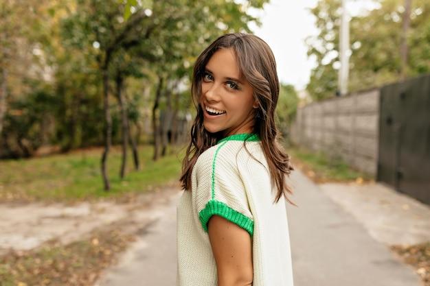 Mulher bonita e charmosa com um sorriso maravilhoso se vira enquanto caminha pela cidade