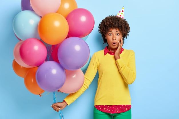 Mulher bonita e chocada segurando balões multicoloridos enquanto posa com um suéter amarelo