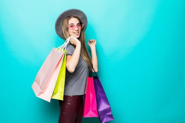 Mulher bonita e compradora sorrindo e usando um chapéu isolado sobre fundo verde