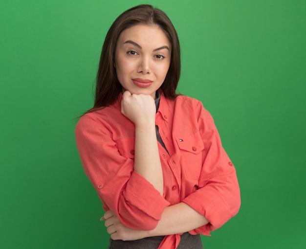Mulher bonita e confiante colocando a mão no queixo, olhando para a frente, isolada na parede verde