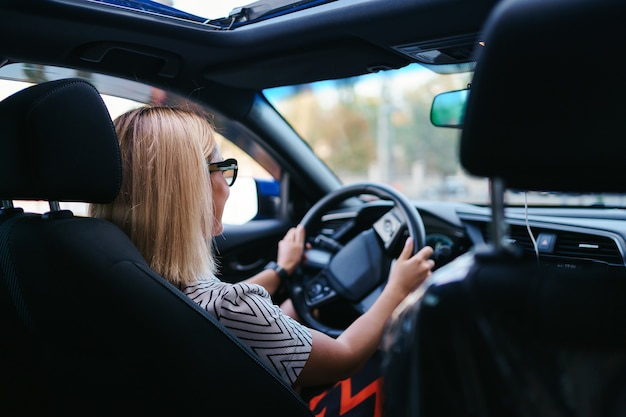 Mulher bonita e confiante em óculos de sol. retrovisor de mulher jovem e atraente em trajes casuais, dirigindo um carro