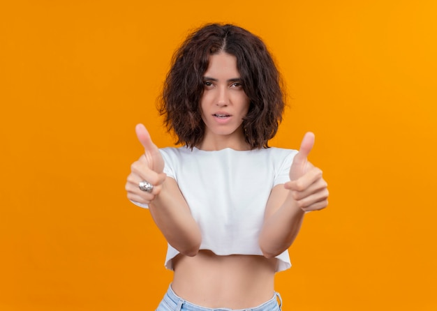 Mulher bonita e confiante mostrando os polegares para cima em uma parede laranja isolada com espaço de cópia