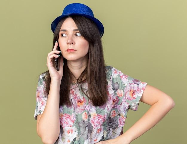 Mulher bonita e desconfiada com chapéu de festa falando no telefone, colocando a mão no quadril, isolada na parede verde oliva