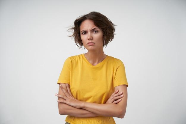 Mulher bonita e desnorteada com cabelo castanho curto franzindo as sobrancelhas e parecendo séria, vestindo uma camiseta amarela enquanto posava com as mãos postas
