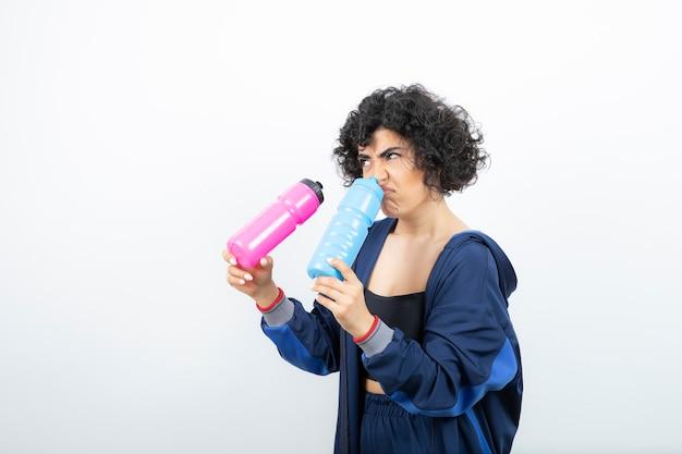 Mulher bonita e desportiva com garrafas de água rosa e azuis em pé.