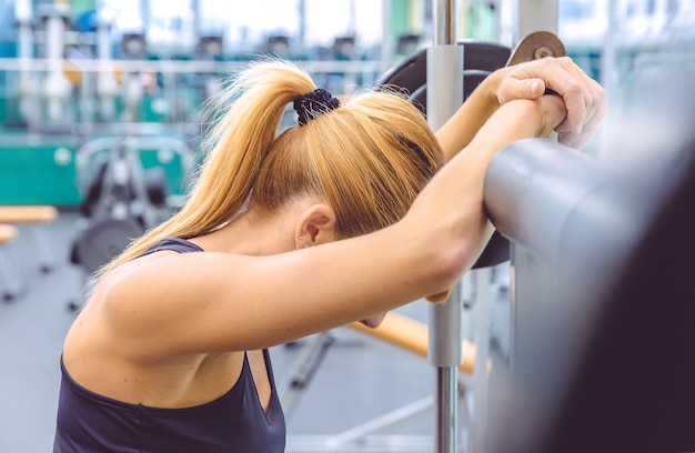 Mulher bonita e desportiva descansando cansada depois de levantar barra em um treinamento muscular no centro de fitness