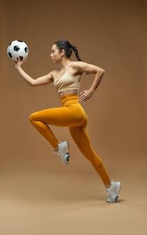 Mulher bonita e desportiva em caneleiras segurando uma bola de futebol e correndo. isolado em fundo bege escuro