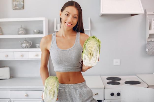 Mulher bonita e desportiva em uma cozinha com legumes