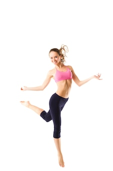 Mulher bonita e desportiva pulando isolado no fundo branco