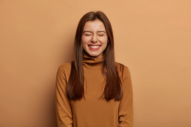Mulher bonita e divertida tem cabelo comprido, escuro e liso, ri de alegria, usa um suéter marrom com gola, sorri afetadamente o rosto