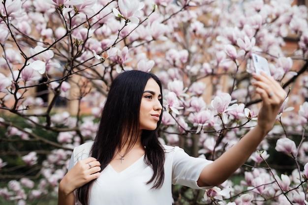 Mulher bonita e elegante caucasiana fazendo selfie no jardim de magnólia em flor. tempo de primavera